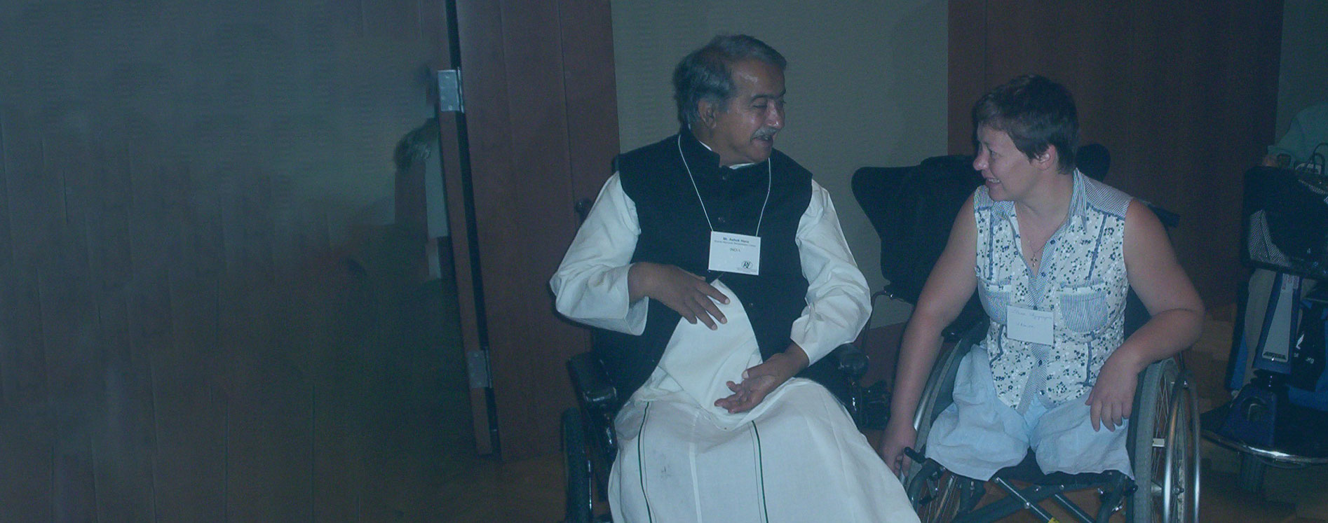 Our Founder Ashok Hans talking with a woman in a wheelchair